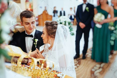 Groom putting a ring on bride's finger during wedding