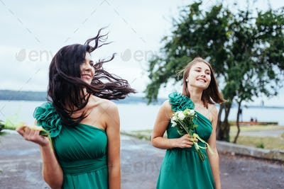 Happy young women at a wedding with bouquets of flowers