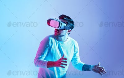 Scary game. Shocked guy in vr glasses sneaks and turns around