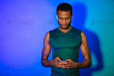 Sporty Black Man Using Phone And Earphones On Blue Background