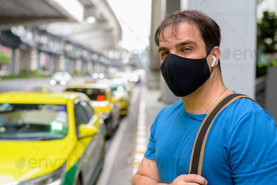 Portrait of Persian man with mask waiting at the taxi station in the city