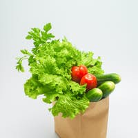 Healthy food. Fresh herbs and vegetables in kraft paper bag on white background