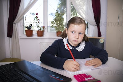 Young girl learn online and looking at laptop at home.Social distancing.