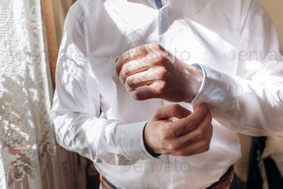stylish groom putting on shirt with cufflinks and tie at the window