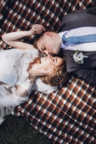 Bride touching groom's face while lying on a blanket in summer outdoors