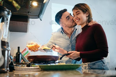 Young Couple Cooking Together And Kissing