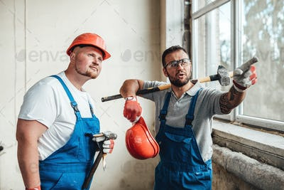 Workers at a construction site, one points with a finger at an object