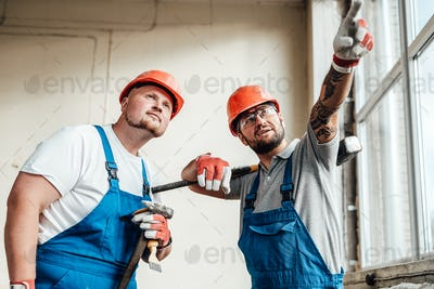 Two workers at a construction site, discussing forthcoming work