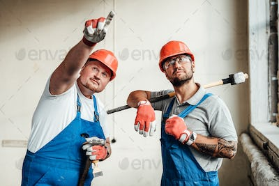 Workers at a construction site, one points at an object, the second one is looking