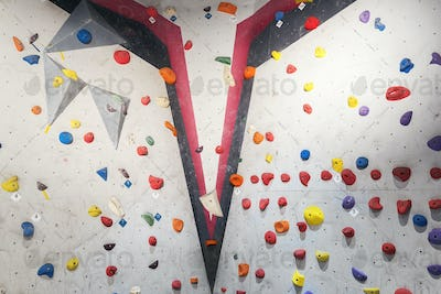 Grey wall with climbing holds and ropes in gym.