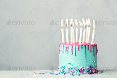 Birthday cake with pink drip icing and ten candles