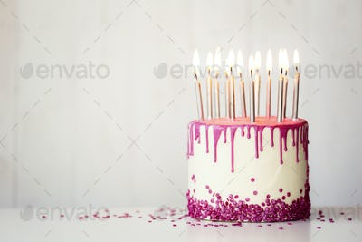 Birthday cake with pink drip icing and candles