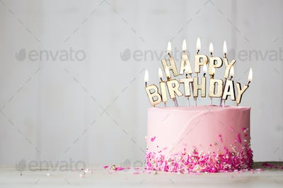 Pink birthday cake with happy birthday candles