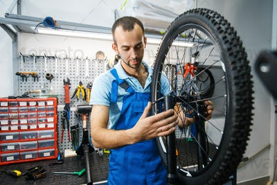 Bicycle assembly in workshop, man setting up chain