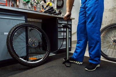 Bicycle assembly in workshop, man inflates wheel