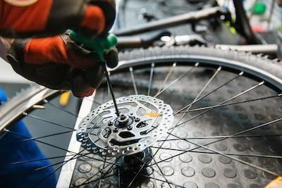 Bicycle assembly in workshop, man installs brake