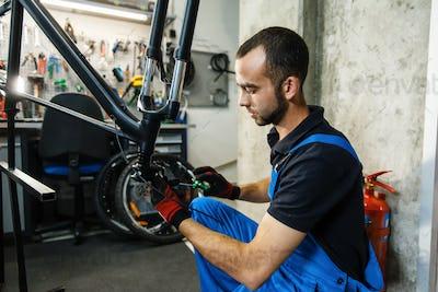 Bicycle repair in workshop, man fixing crank