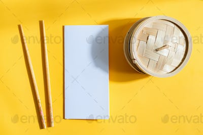 Mock-up paper brochure with wooden sticks and wicker box