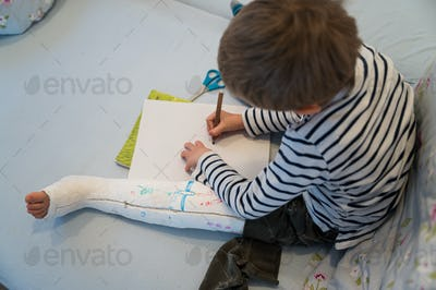 Toddler boy with his leg in a cast drawing on white piece of paper