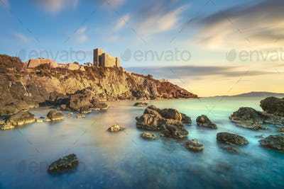 Talamone rocky beach and medieval fortress at sunset. Maremma Argentario, Tuscany, Italy