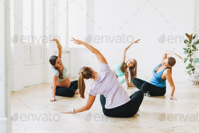 Group of pregnant women in sports uniforms with coach doing gymnastic