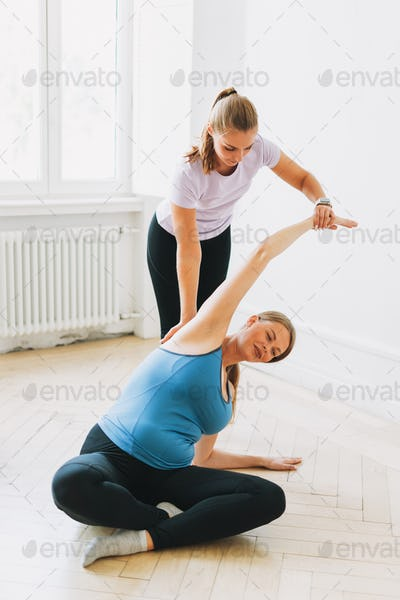 Pregnant woman in sports uniforms with coach doing gymnastic in bright studio