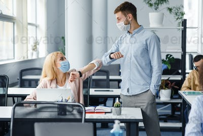 Modern greeting at office during coronavirus epidemic. Young man and woman in protective masks touch