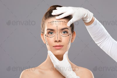 Young woman with face marks getting treatment at beauty clinic