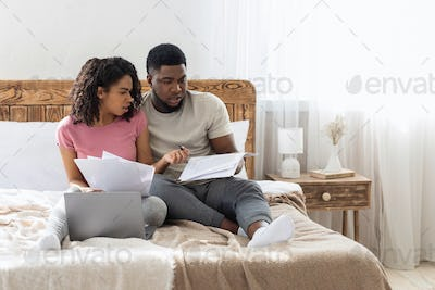 African american young couple checking family budget on weekend
