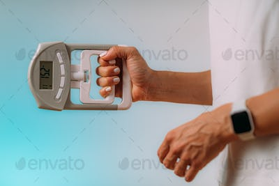 Woman with Digital Hand Grip Dynamometer, Measuring Strength