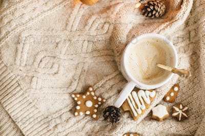 Warm coffee on background of cozy knitted sweater, christmas gingerbread cookies, lights