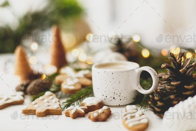 Christmas gingerbread cookies, coffee, pine cones  and warm lights on white wooden table