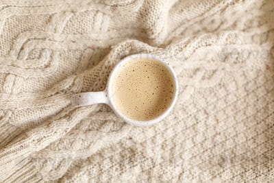 Warm coffee in stylish cup on cozy knitted sweater, top view
