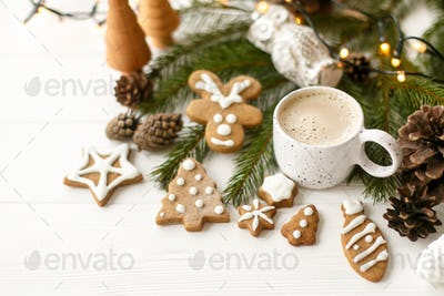 Coffee in stylish cup with gingerbread cookies, pine cones and warm lights on white wooden table