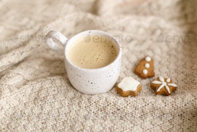 Warm coffee in stylish cup on cozy knitted sweater with christmas gingerbread cookies