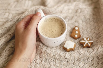 Hand holding warm coffee on background of cozy knitted sweater with christmas gingerbread cookies