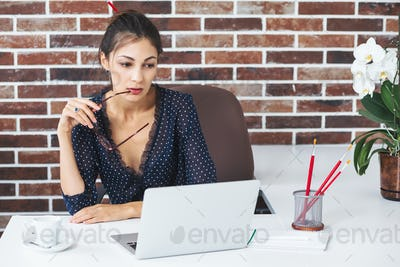 Business woman in the office at the desk with laptop thinking