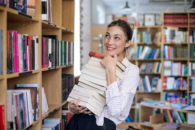 Happy young woman with a stack of books in library