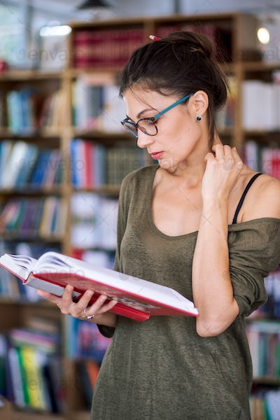 Young simpatic woman reading a book