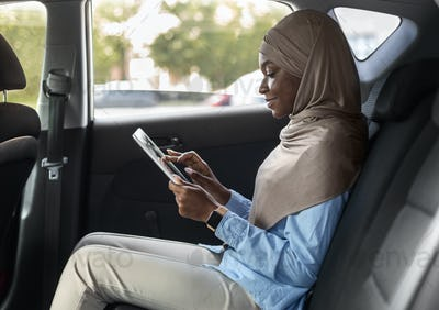 Beautiful black islamic businesswoman using digital tablet in car, going to work
