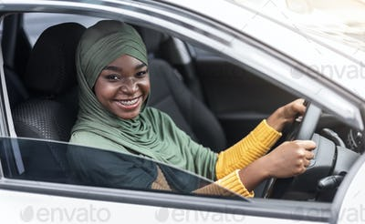 Young african muslim lady driver sitting on front seat in modern car