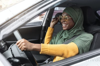 First Car. Cheerful Young Black Muslim Woman In Hijab Driving New Auto