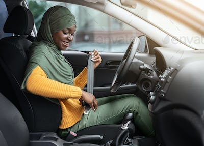 Safety First. Smiling Black Muslim Woman In Hijab Fastening Seatbelt In Car
