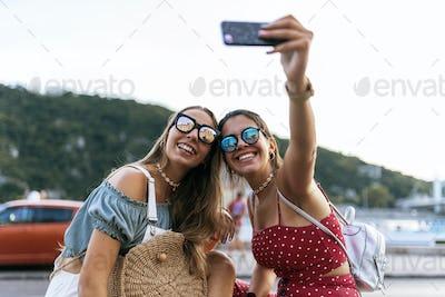 Cheerful women sitting on bridge and using cellphone