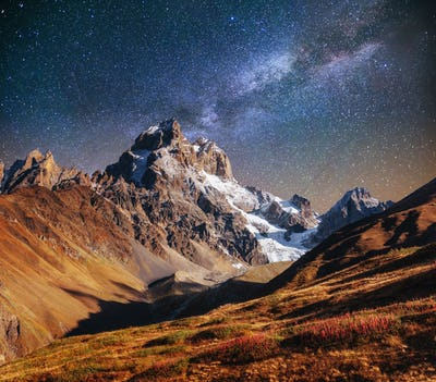 Fantastic starry sky. Autumn landscape and snow-capped peaks. Ma