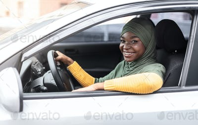 Car Insurance Concept. Smiling african muslim woman sitting in modern vehicle