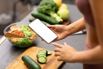 Woman Using Smartphone Cooking Healthy Dinner For Weight-Loss In Kitchen