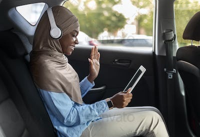 Distant Communication. Muslim businesswoman making video call with digital tablet in car