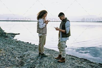 Couple using gadgets at lake