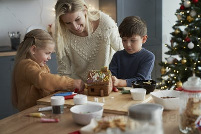 Children and mother decorating gingerbread house in the kitchen